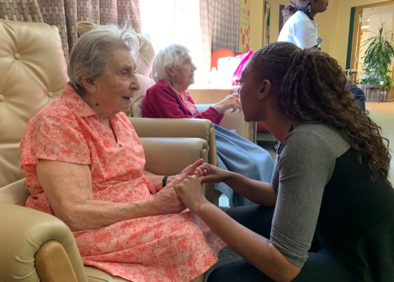Elderly resident of Nightingale Hammerson Care Home with carer